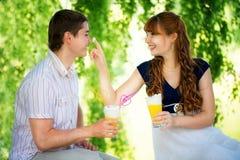 Pares jovenes hermosos que se divierten Comida campestre en campo Feliz Imagen de archivo libre de regalías
