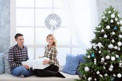 Pares jovenes hermosos que se sientan por la ventana con las decoraciones y el árbol de navidad del ` s del Año Nuevo Imagenes de archivo