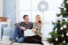 Pares jovenes hermosos que se sientan por la ventana con las decoraciones y el árbol de navidad del ` s del Año Nuevo Fotografía de archivo