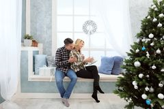 Pares jovenes hermosos que se sientan por la ventana con las decoraciones y el árbol de navidad del ` s del Año Nuevo Fotos de archivo libres de regalías