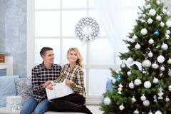 Pares jovenes hermosos que se sientan por la ventana con las decoraciones y el árbol de navidad del ` s del Año Nuevo Fotos de archivo