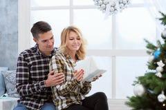 Pares jovenes hermosos que se sientan por la ventana con las decoraciones y el árbol de navidad del ` s del Año Nuevo Imagen de archivo