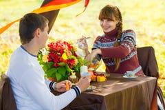 Pares jovenes hermosos que tienen comida campestre en parque del otoño Famil feliz Imagen de archivo libre de regalías