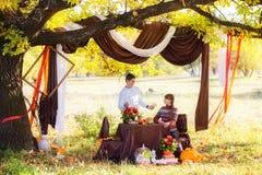 Pares jovenes hermosos que tienen comida campestre en parque del otoño Famil feliz Fotografía de archivo