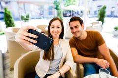 Pares jovenes hermosos que toman el selfie mientras que se sienta en el café Imágenes de archivo libres de regalías