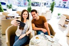 Pares jovenes hermosos que toman el selfie mientras que se sienta en el café Foto de archivo libre de regalías