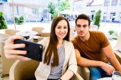 Pares jovenes hermosos que toman el selfie mientras que se sienta en el café Imagen de archivo libre de regalías