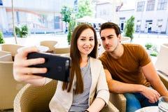 Pares jovenes hermosos que toman el selfie mientras que se sienta en el café Fotografía de archivo