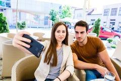 Pares jovenes hermosos que toman el selfie mientras que se sienta en el café Fotos de archivo