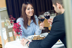 Pares jovenes hermosos que tuestan las copas de vino en el restaurante Foto de archivo