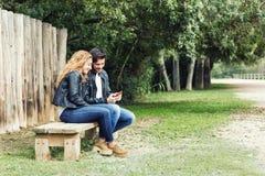 Pares jovenes hermosos usando ellos teléfono móvil en el parque Imágenes de archivo libres de regalías