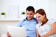 Pares jovenes hermosos usando la computadora portátil junto Fotos de archivo