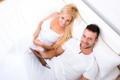 Pares jovenes hermosos usando un Tablet PC en cama Foto de archivo libre de regalías