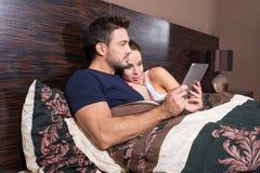 Pares jovenes hermosos usando un Tablet PC en cama Fotos de archivo