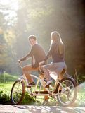Pares jovenes, hombre hermoso y mujer atractiva en la bici en tándem en parque o bosque soleado del verano fotografía de archivo libre de regalías