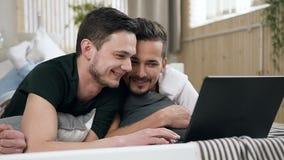Pares jovenes homosexuales que miran película divertida en el ordenador portátil que miente en cama Pares gay amuseding caucásico metrajes