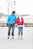 Pares jovenes iceskating al aire libre Imagen de archivo libre de regalías
