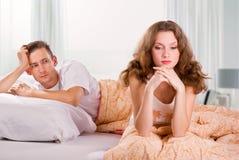 Pares jovenes infelices en dormitorio Fotos de archivo