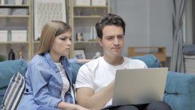 Pares jovenes infelices frustrados que reaccionan a la pérdida en el ordenador portátil almacen de metraje de vídeo