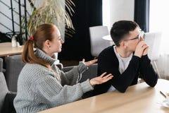 Pares jovenes infelices que discuten, esposa enojada que mira al marido que lo culpa de los problemas, conflictos en el matrimoni fotos de archivo libres de regalías