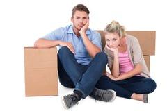 Pares jovenes infelices que se sientan al lado de las cajas móviles Imagen de archivo libre de regalías