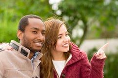 Pares jovenes interraciales felices hermosos y sonrientes en el parque, mujer que señala en alguna parte en un fondo del parque Foto de archivo