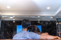 Pares jovenes junto que miran el sofá que se sienta de la TV en la sala de estar en casa feliz Foto de archivo libre de regalías