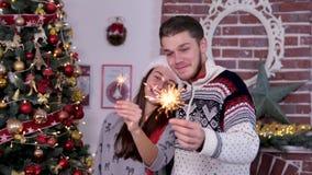 Pares jovenes lindos con el sombrero divertido de santa y las bengalas rojos el sostenerse, celebrando Feliz Navidad almacen de metraje de vídeo