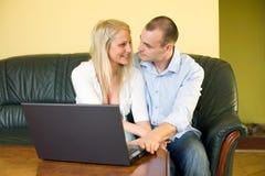 Pares jovenes lindos con la computadora portátil en el país. Fotografía de archivo