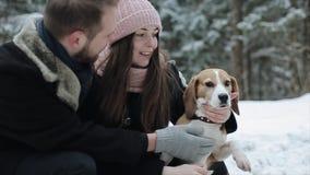 Pares jovenes lindos del inconformista que se divierten en parque del invierno con su perro en un día y una sonrisa brillantes El almacen de metraje de vídeo