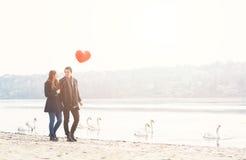 Pares jovenes lindos en el amor, caminando en la orilla, con un globo rojo Imagen de archivo