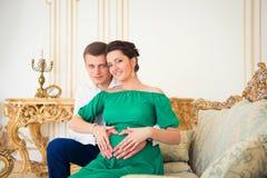 Pares jovenes lindos que abrazan blando la panza embarazada Imagen de archivo libre de regalías