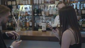 Pares jovenes lindos que se sientan en la barra en un restaurante costoso o un pub El hombre confiado barbudo bebe el whisky y su almacen de video