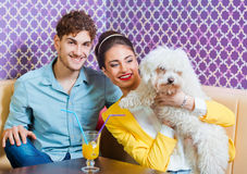 Pares jovenes lindos que se sientan en la tabla con un perrito Fotografía de archivo libre de regalías