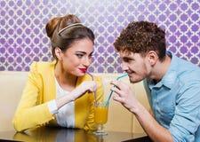 Pares jovenes lindos que se sientan en la tabla que comparte una bebida Imágenes de archivo libres de regalías