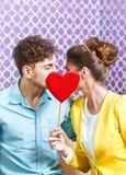Pares jovenes lindos que se sientan en la tabla que se besa detrás de un corazón Foto de archivo