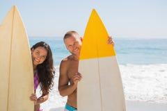 Pares jovenes lindos que sostienen sus tablas hawaianas Fotografía de archivo libre de regalías