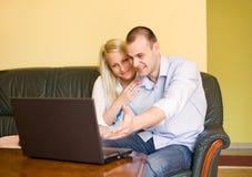 Pares jovenes lindos usando red a través de la computadora portátil. Fotos de archivo