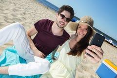 Pares jovenes magníficos que se sientan en la playa y que hacen el selfie Fotografía de archivo