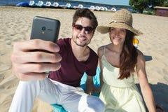 Pares jovenes magníficos que se sientan en la playa y que hacen el selfie Imagen de archivo