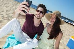Pares jovenes magníficos que se sientan en la playa y que hacen el selfie Imagenes de archivo