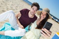 Pares jovenes magníficos que se sientan en la playa y que hacen el selfie Fotos de archivo libres de regalías