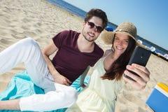 Pares jovenes magníficos que se sientan en la playa y que hacen el selfie Foto de archivo libre de regalías