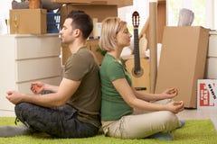 Pares jovenes meditating en nueva casa Foto de archivo libre de regalías