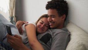Pares jovenes multiétnicos atractivos que se relajan en dormitorio con el smartphone que se abraza Tiro a cámara lenta almacen de metraje de vídeo