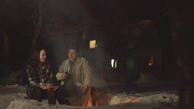Pares jovenes por el fuego con la cerveza metrajes