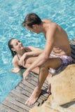 Pares jovenes por la piscina Imágenes de archivo libres de regalías