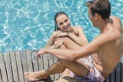 Pares jovenes por la piscina Imagenes de archivo