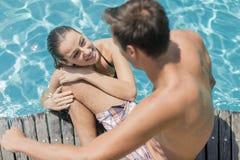 Pares jovenes por la piscina Foto de archivo