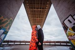 Pares jovenes por la tarde debajo del puente Fotos de archivo libres de regalías